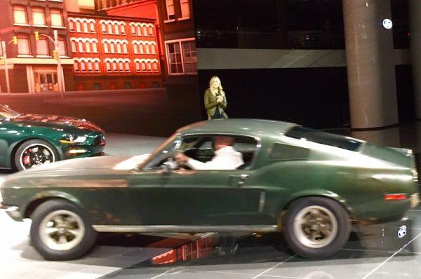 Sean Kiernan driving the Bullitt on to the Ford stage - Steve's Granddaughter, Molly McQueen standing