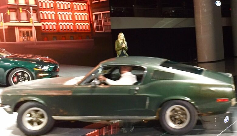 Sean Kiernan driving the Bullitt on to the Ford stage - Steve's Granddaughter, Molly McQueen standing