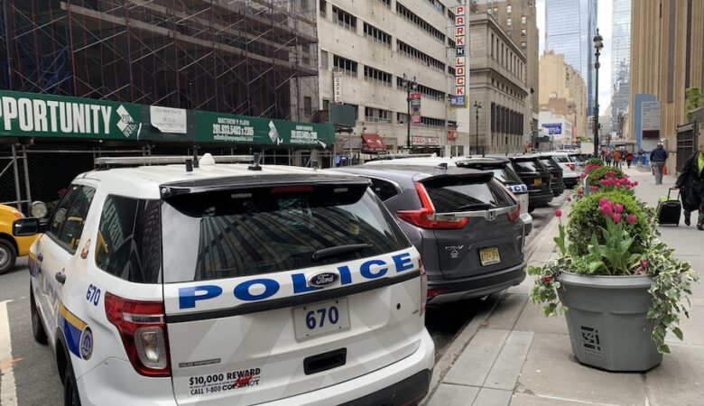 white Ford SUV and minivans with blue and yellow writing on the police vehicles